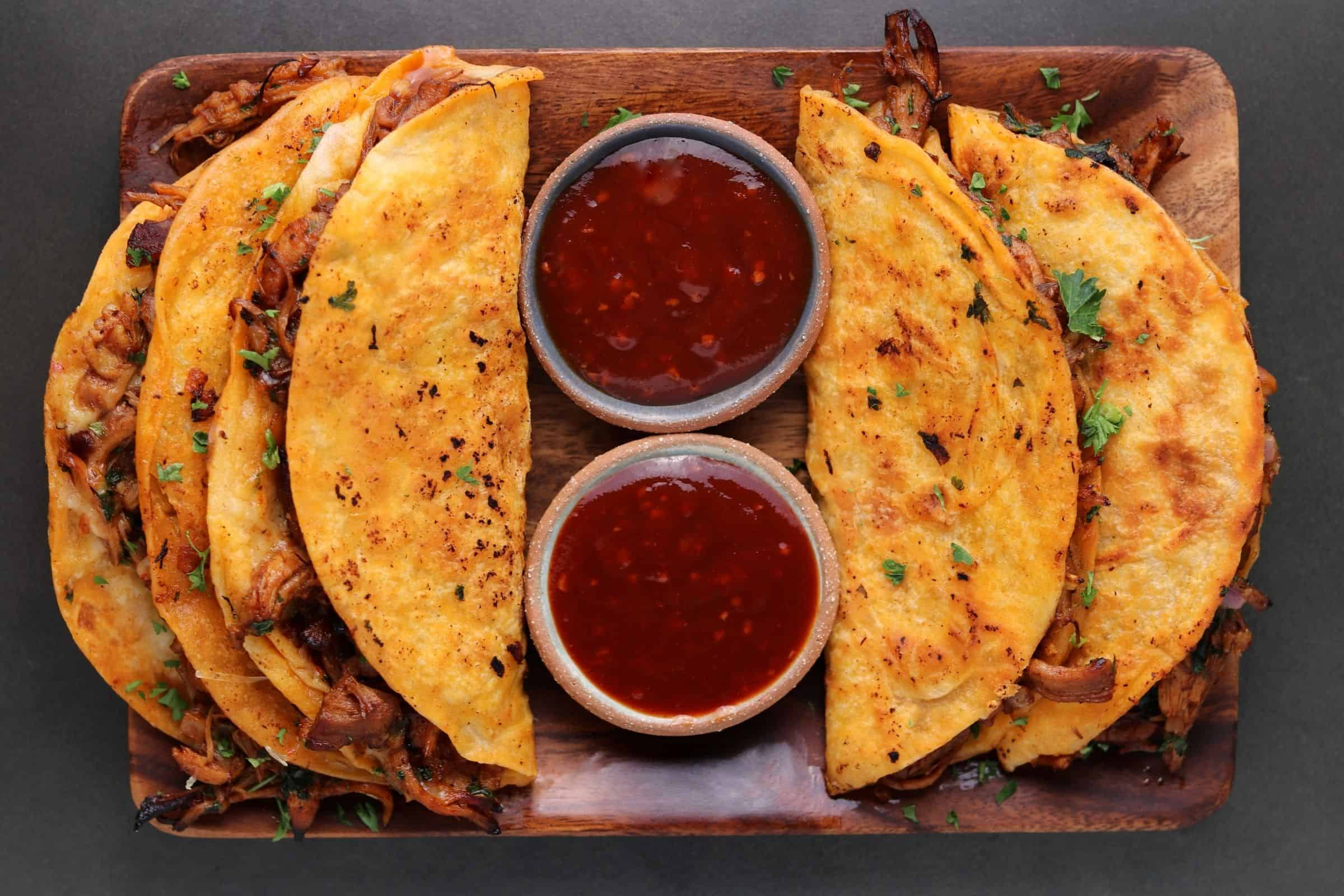 four bbq chicken quesadillas on a wooden tray with two bowls of bbq sauce