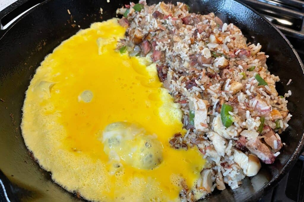 beaten eggs added to one side of the skillet