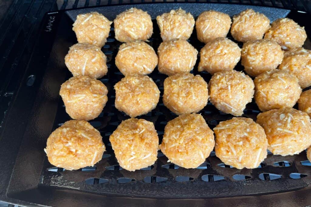 meatballs on a cast iron grill topper inside the Traeger