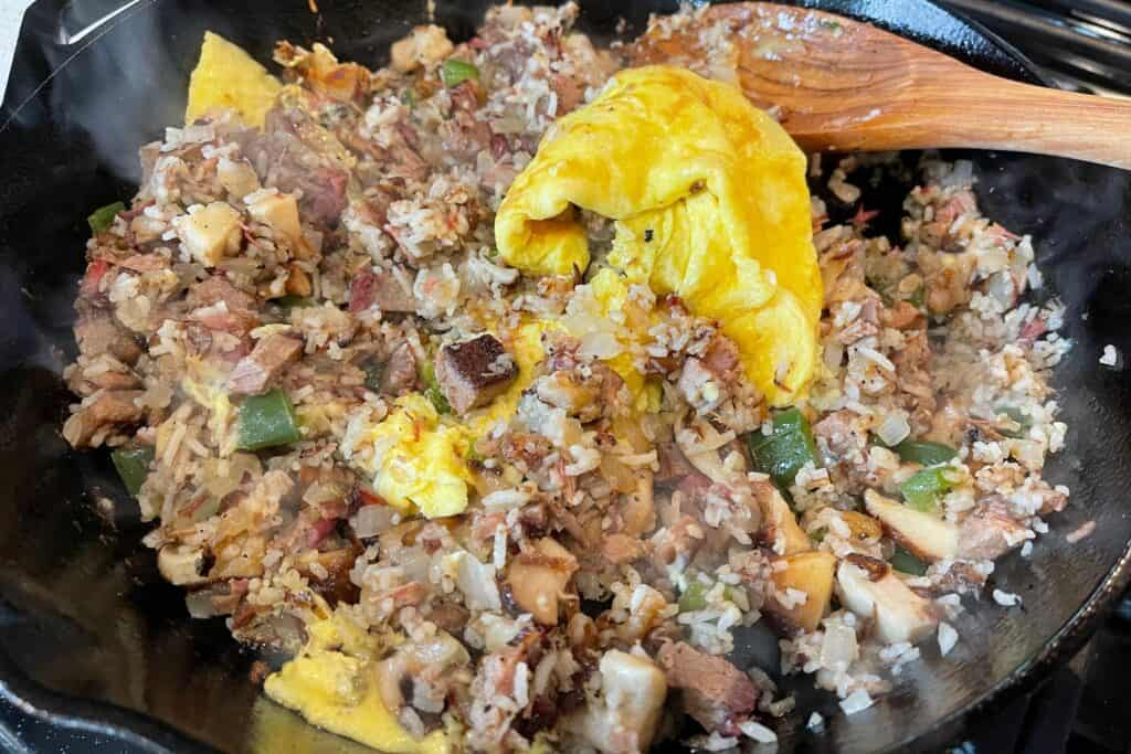 cooking the eggs into the brisket fried rice