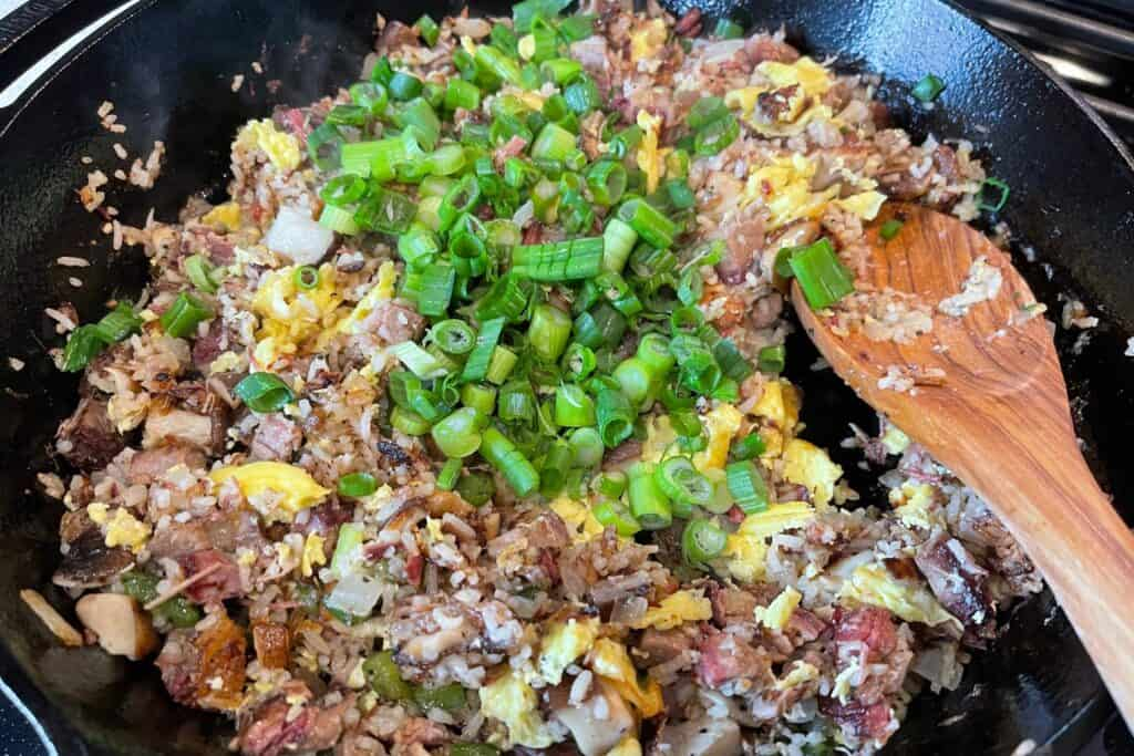 green onion going in the brisket fried rice