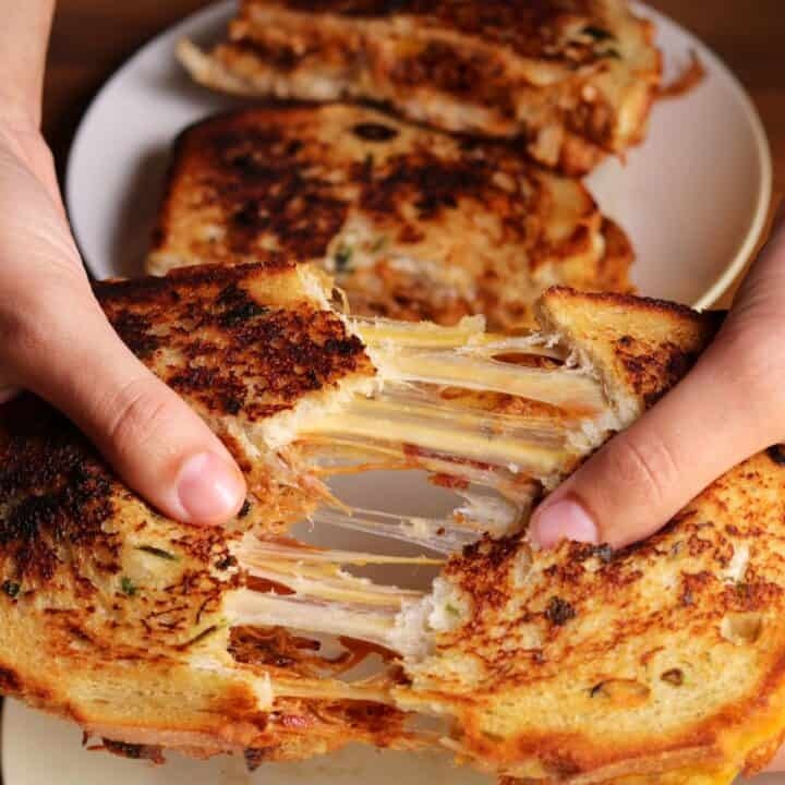 pulling apart a pulled pork grilled cheese by hand