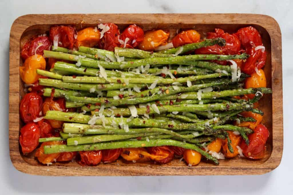 asparagus and tomatoes on a brown plate with grated parmesan