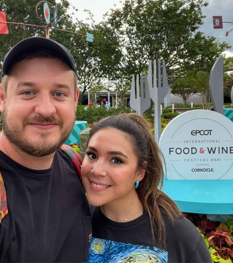 the Woodruffs in front of the EPCOT Food & Wine Festival 2021 sign
