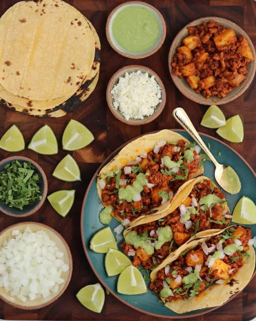 three ground pork tacos al pastor with diced white onion, cilantro, lime wedges, salsa verde, queso fresco, and corn tortillas