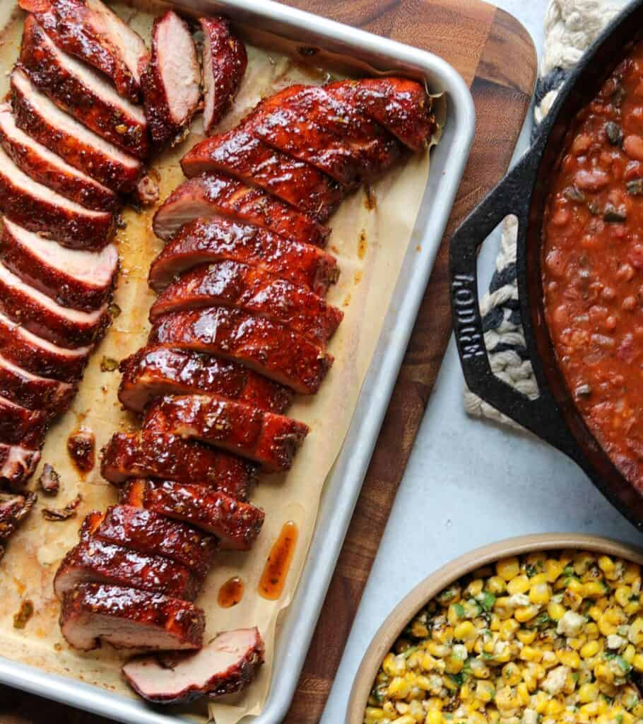 finished and sliced pork on a sheet pan beside a cast iron skillet with smoked charro beans and a bowl of Mexican street corn salad