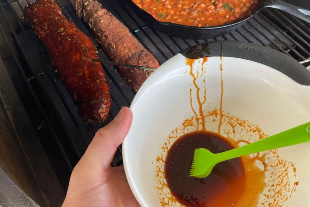 two pork tenderloins on the Traeger grill with a hot sauce and brown sugar glaze being brushed on
