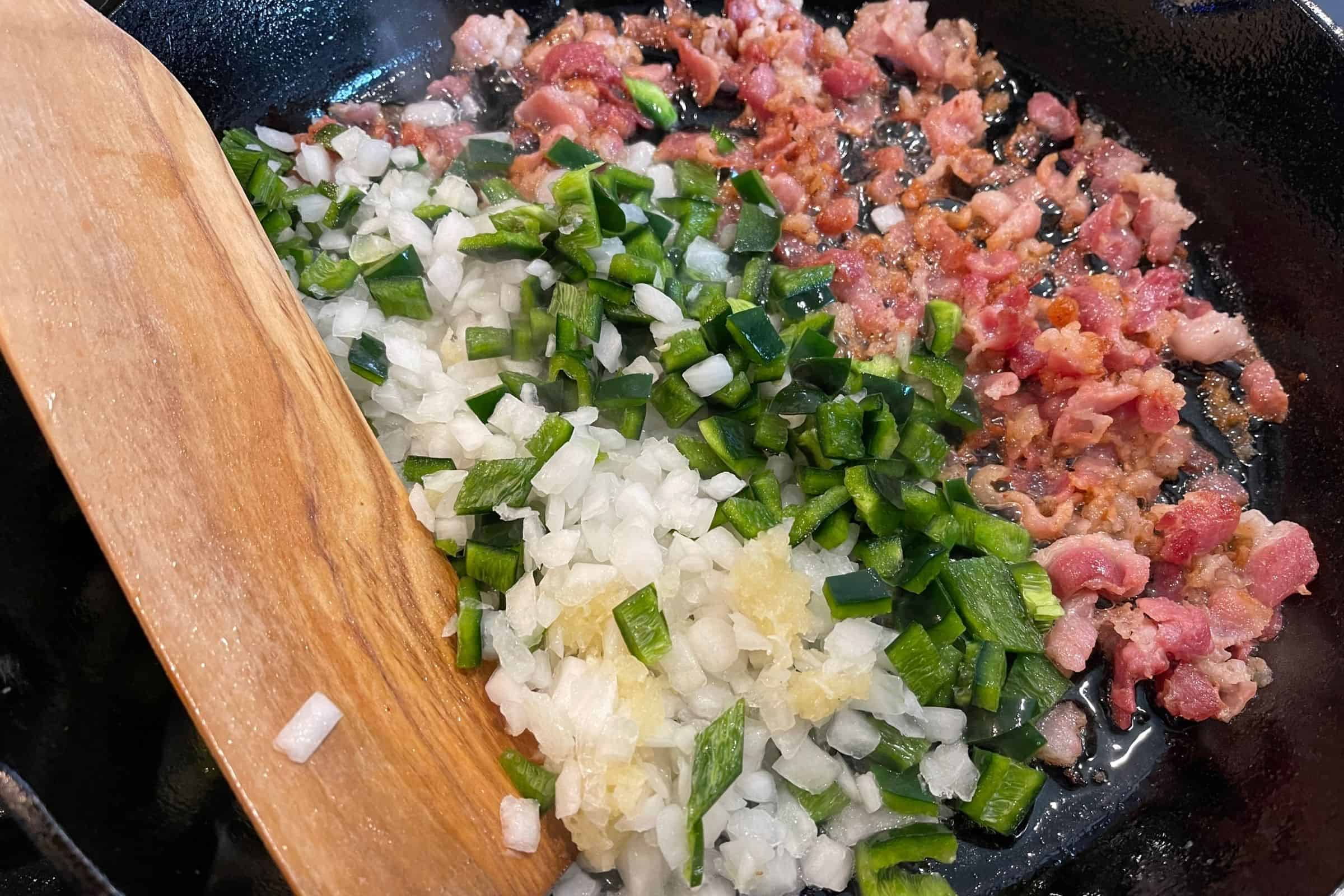 rendered bacon fat in a cast iron skillet with onion, poblano, and garlic