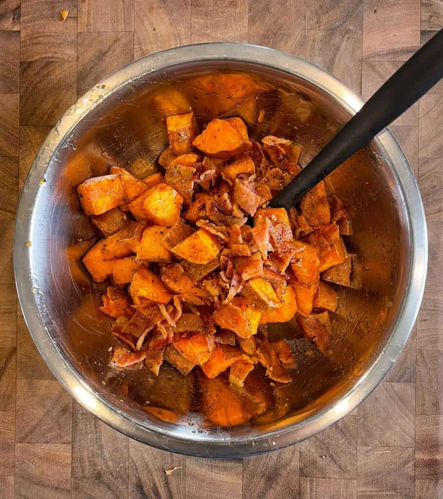 air fried sweet potatoes and chopped bacon in a mixing bowl