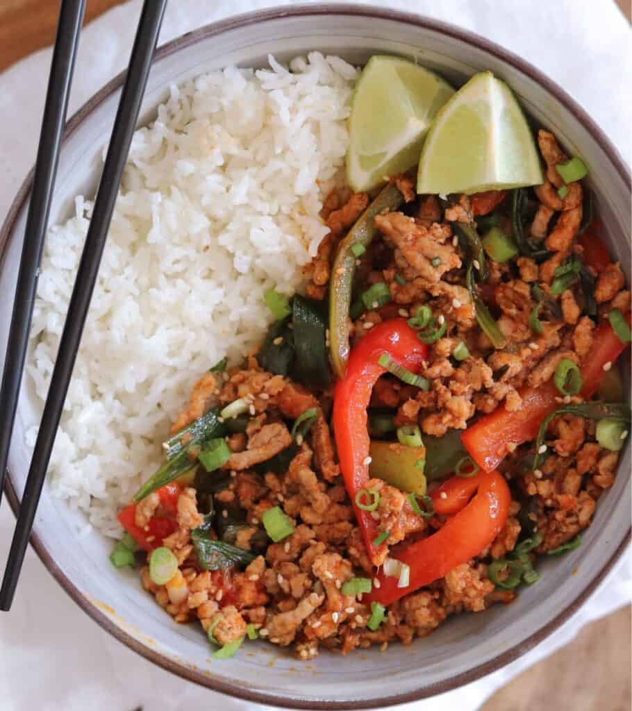 ground pork stir fry in a bowl with rice and lime wedges